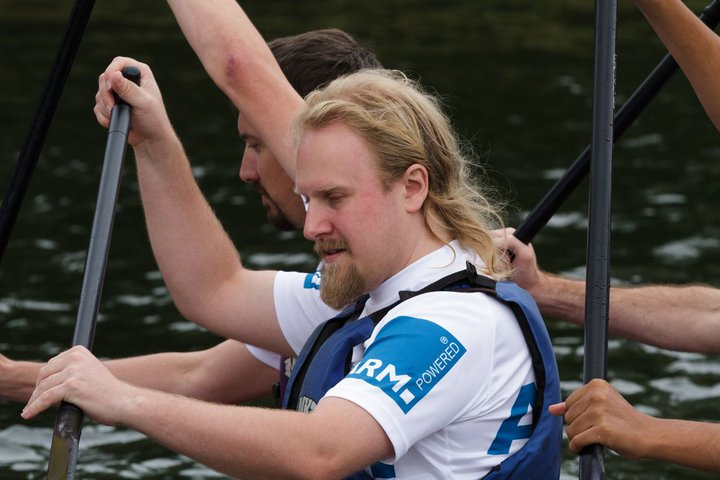 Me in a dragon boat, holding a paddle, wearing a t-shirt that says 'ARM Powered' on the sleeve...